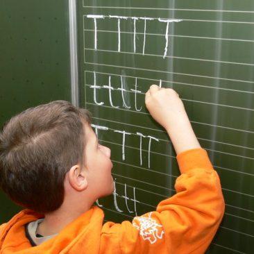 Buchstabe in die Lineatur an der Tafel schreiben